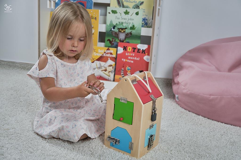 dziewczynka trzyma w rączkach łańcuch od zamka drewnianego domku
