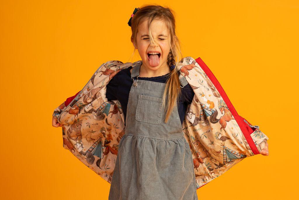 dziewczynka wytyka język rozkładając przy tym kurteczkę w fantazyjne wzory na boki