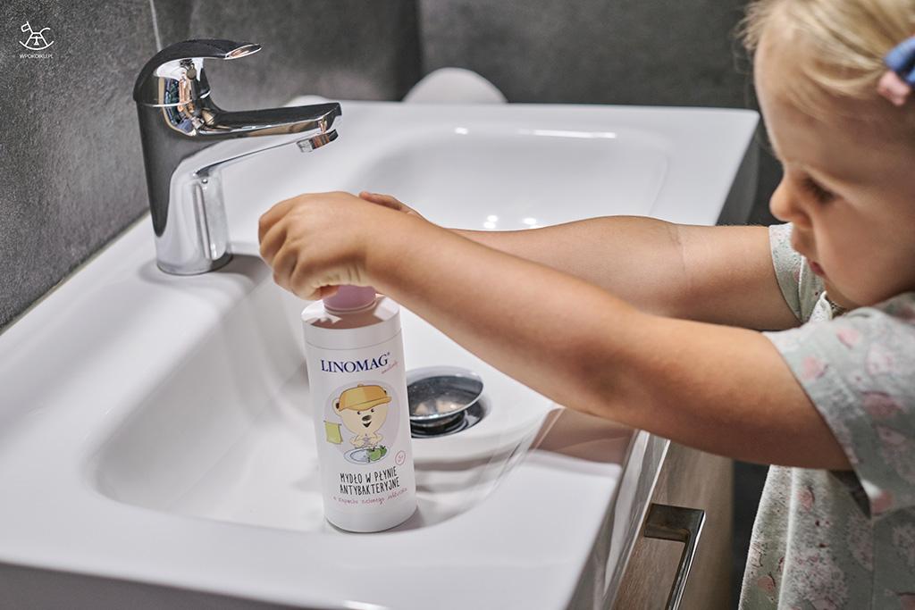 dziewczynka z pomocą pompki nabiera mydła do mycia rączek w łazience