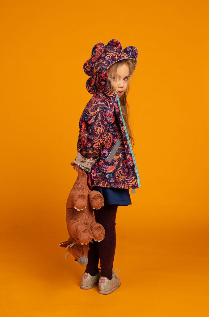 dziewczynka w kurteczce stoi tyłem i obraca się w kierunku aparatu trzymając w rękach pluszowego dinozaura