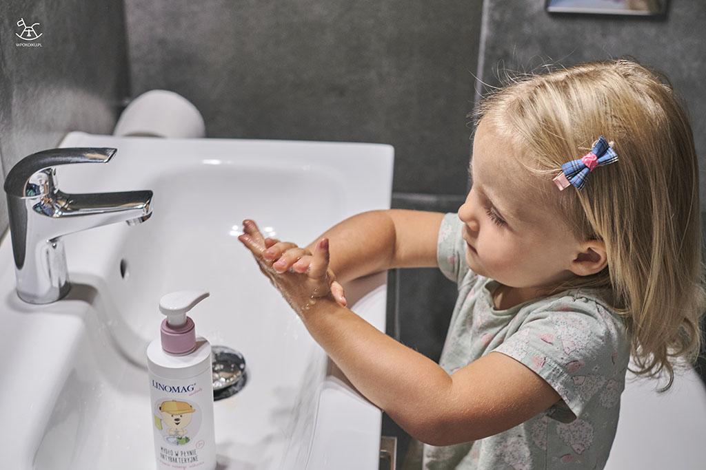 mała dziewczynka myje rączki w łazience z pomocą mydła w płynie