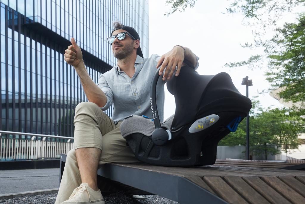 mężczyzna siedzi obok fotelika samochodowego na ławce