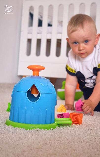 na pierwszym planie domek, a chłopiec siedzi w tle szukając klocków