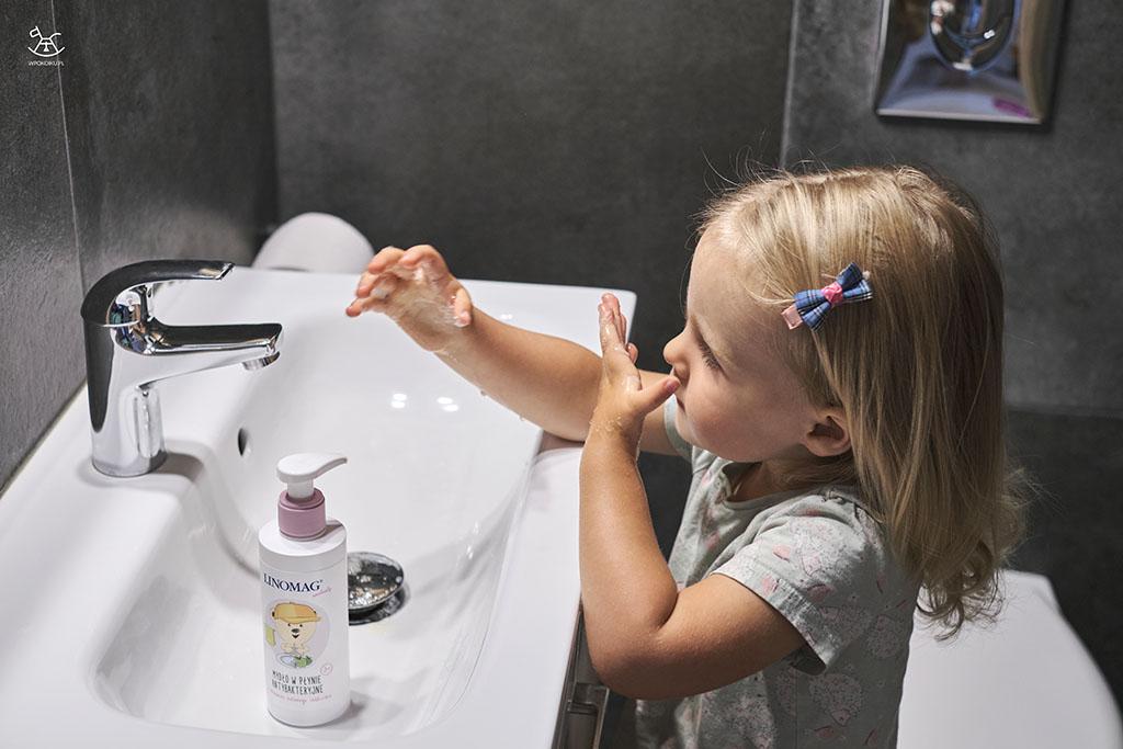 podczas mycia rączek dziewczynka sprawdza zapach mydełka