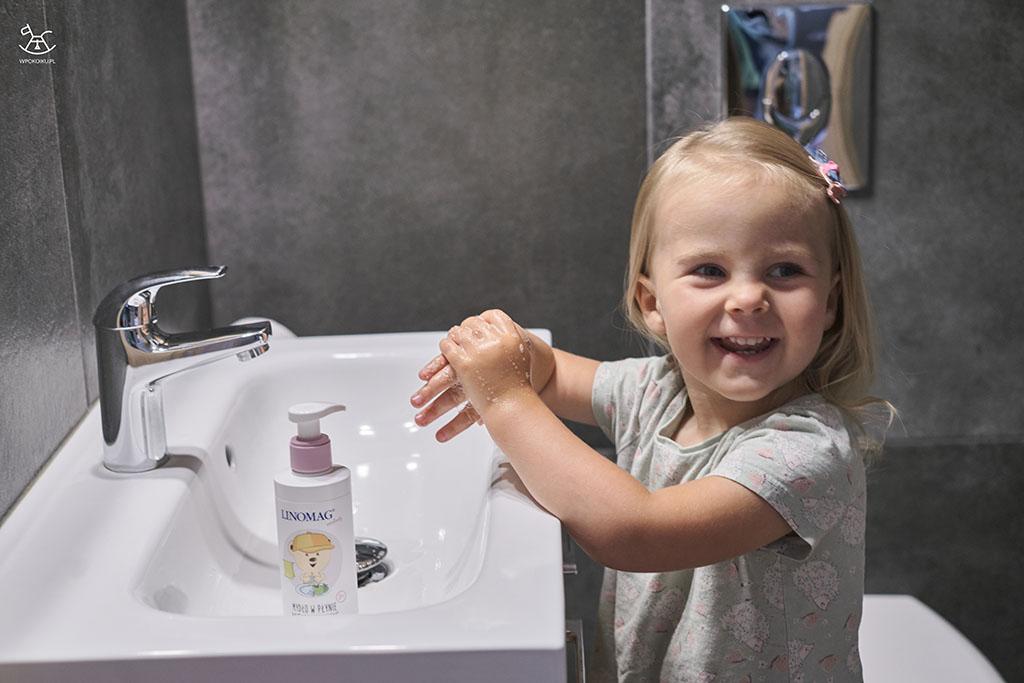 szeroko uśmiechnięta dziewczynka podczas mycia rąk mydełkiem w łazience