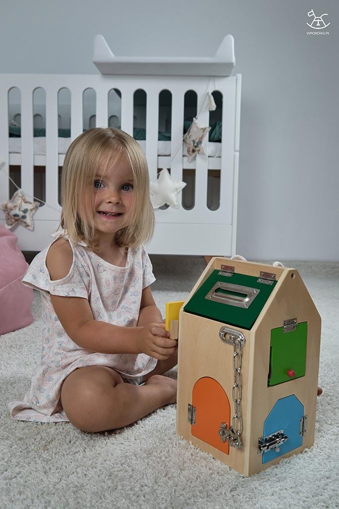 uśmiechnięta dziewczynka bawi się drewnianym domkiem