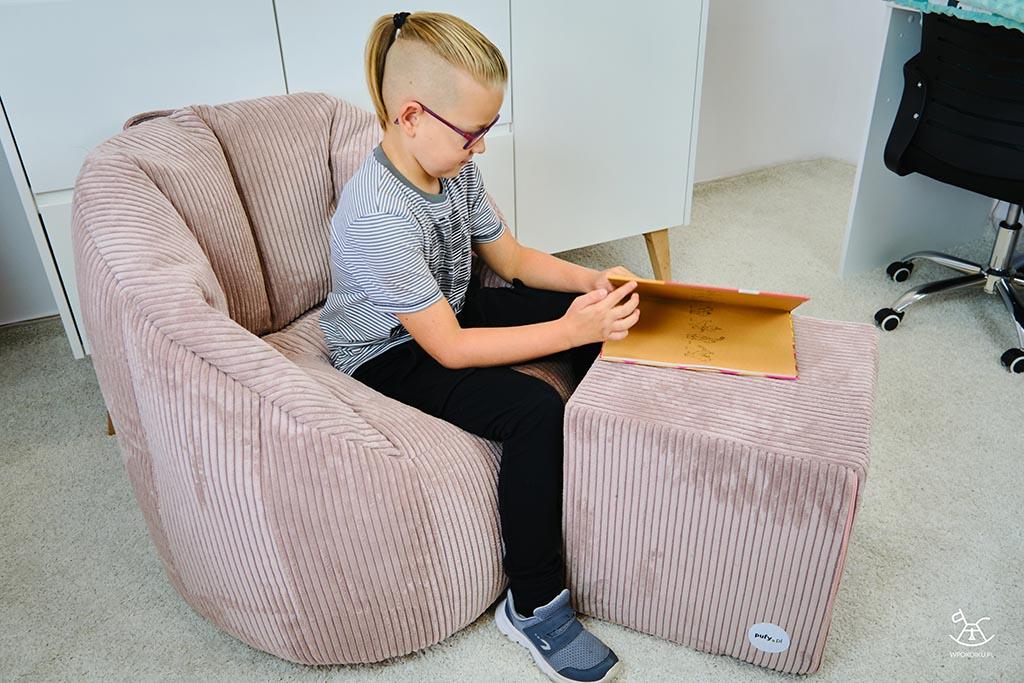 Sztruksowe pufy w brudnoróżowym kolorze, na których siedzi chłopiec