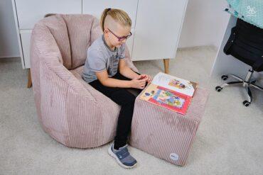 chłopczyk siedzi na pufach i czyta książeczkę w pokoju