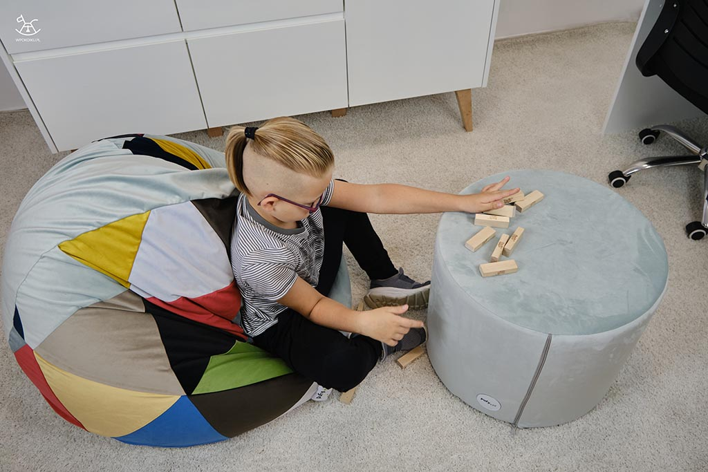 chłopiec bawi się klockami na pufach