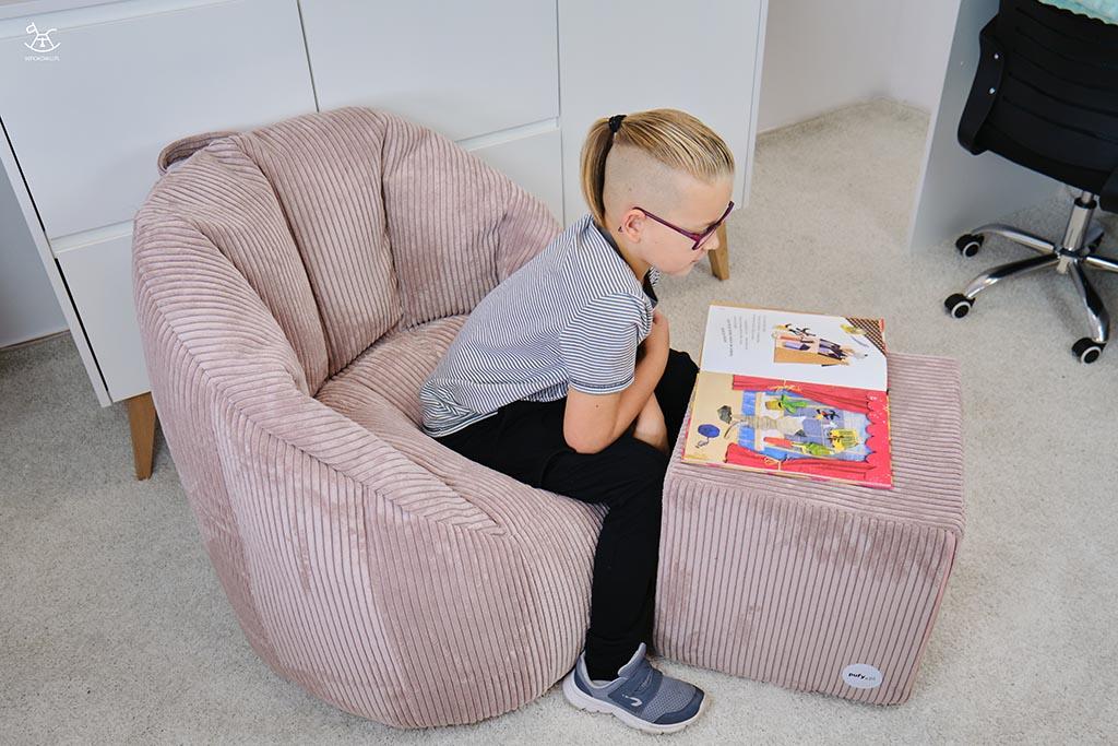 chłopiec czyta książkę na sztruksowych pufach