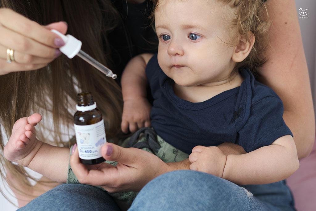 chłopiec patrzy z zaciekawieniem na kroplomierz z witaminą