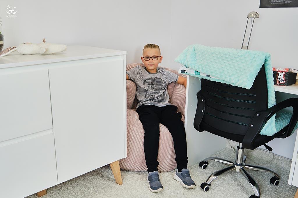 chłopiec siedzi na pufie w kryjówce między meblami