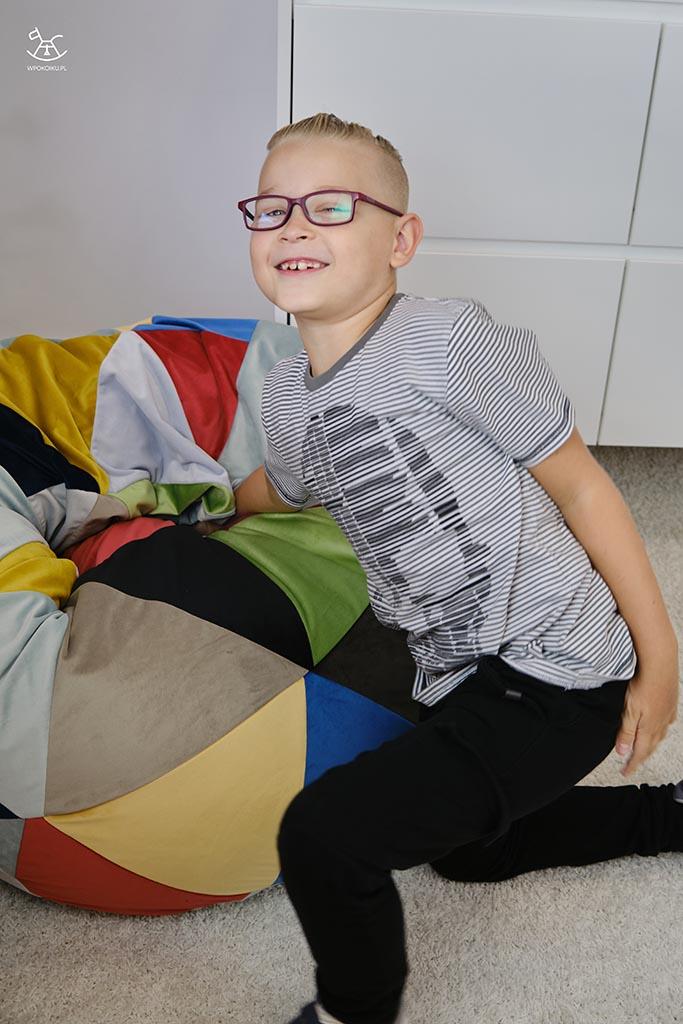 dziecko bawi się na kolorowej pufie