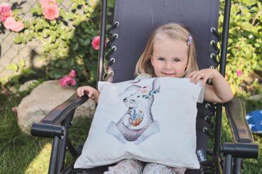 dziewczynka siedzi na krześle w ogrodzie z poduszką