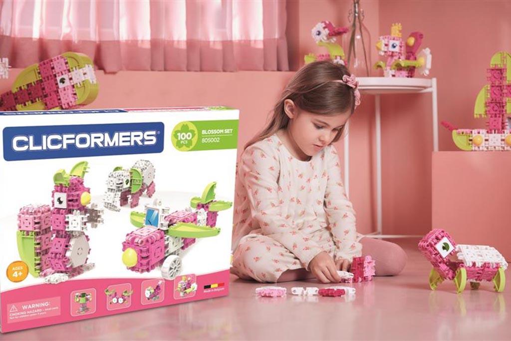 dziewczynka w różowym pokoju z zestawem klocków