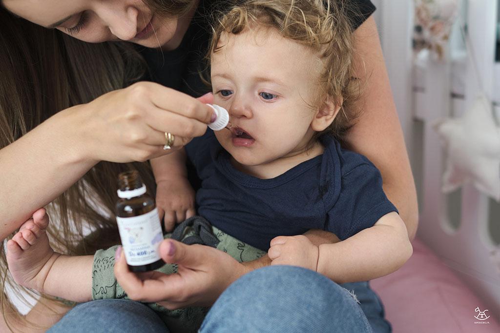 mama podaje dziecku krople z witaminą