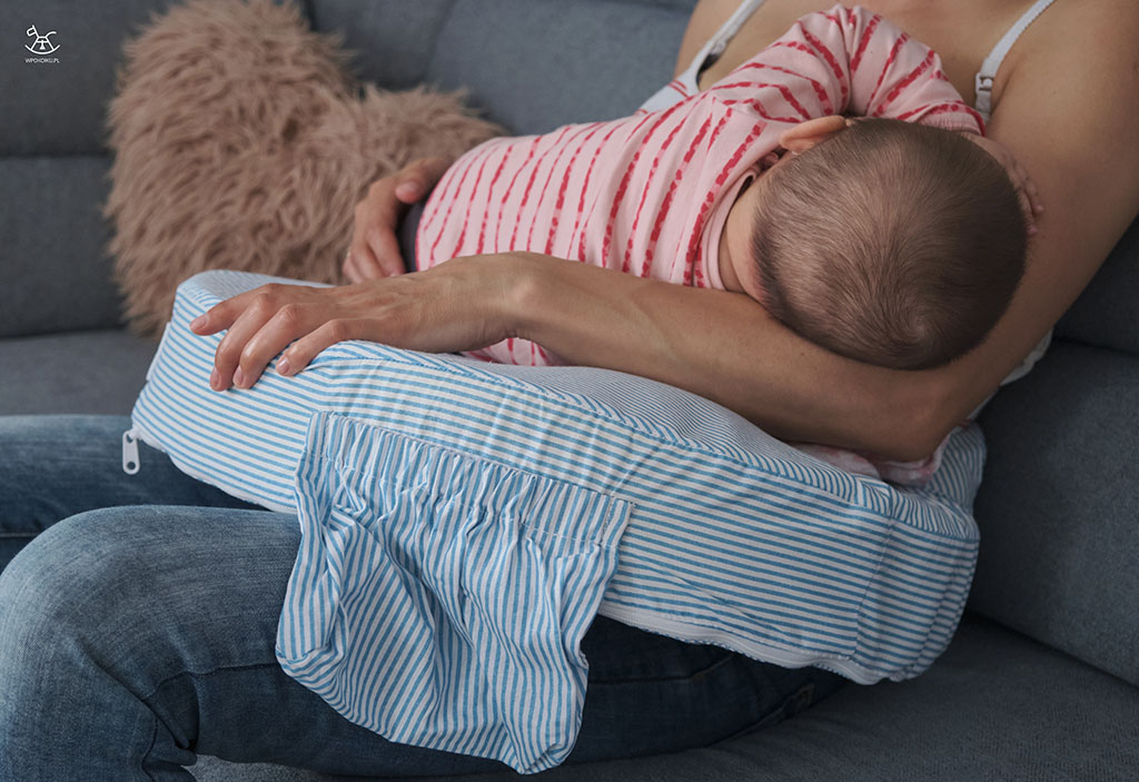 mama trzyma dziecko na poduszce do karmienia