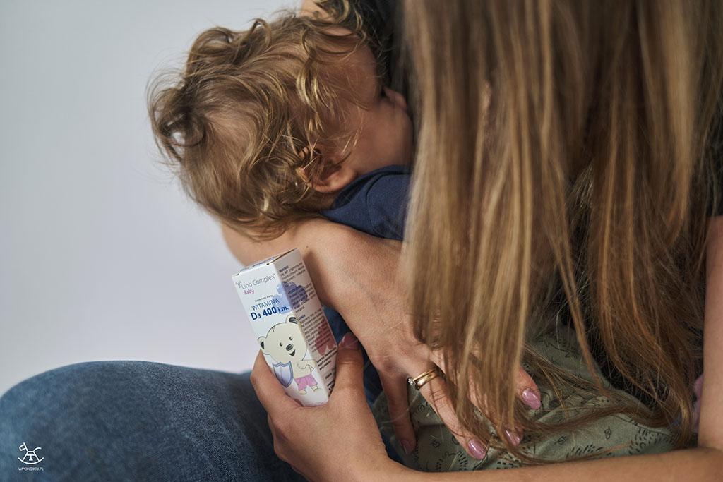 mama trzyma opakowanie z suplementami karmiąc dziecko