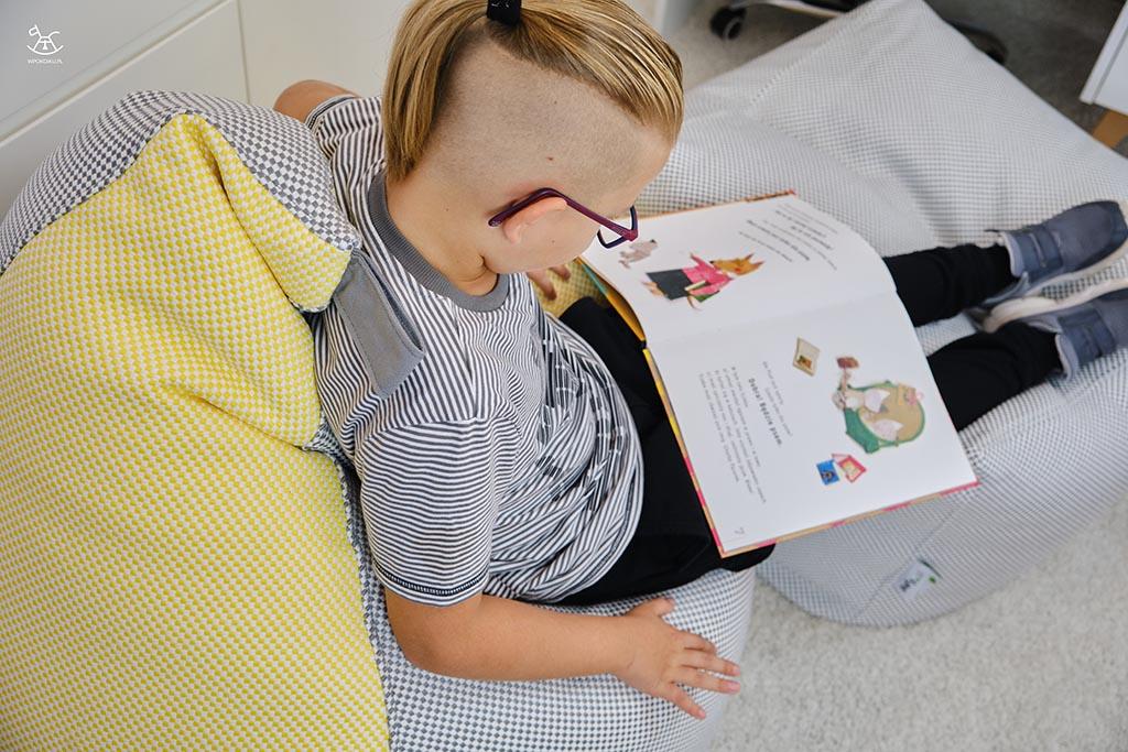 rzut od góry na chłopca czytającego na pufach