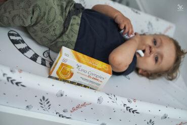 suplementy z witaminą d3 obok dziecka leżącego na przewijaku