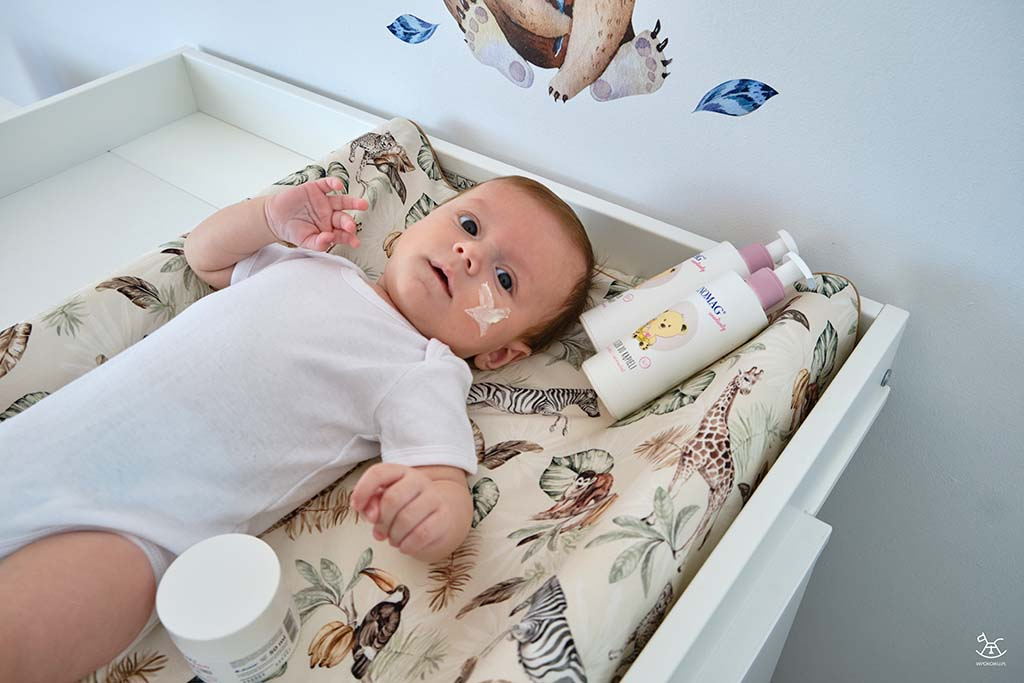 niemowlak na przewijaku z kremem na buzi