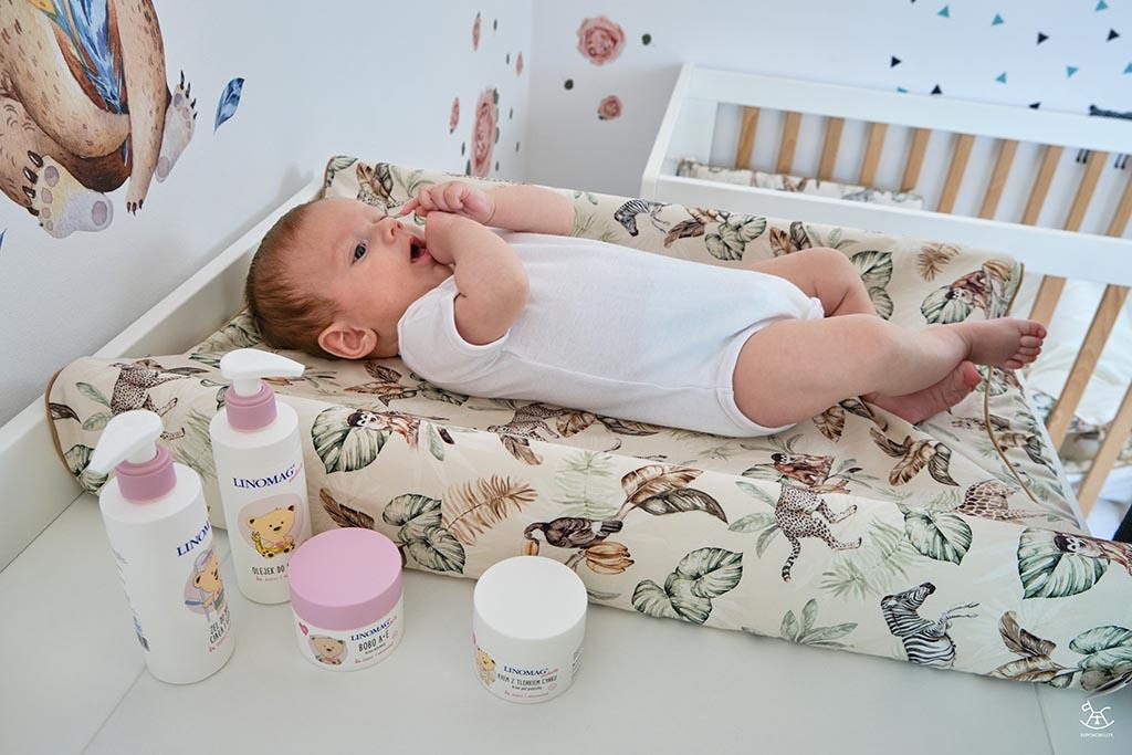 niemowlę leżące na przewijaku z kosmetykami do pielęgnacji