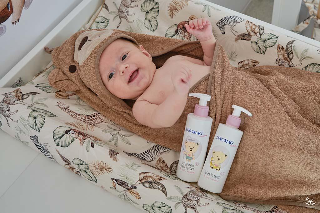 uśmiechnięte dziecko na przewijaku z kosmetykami do kąpieli